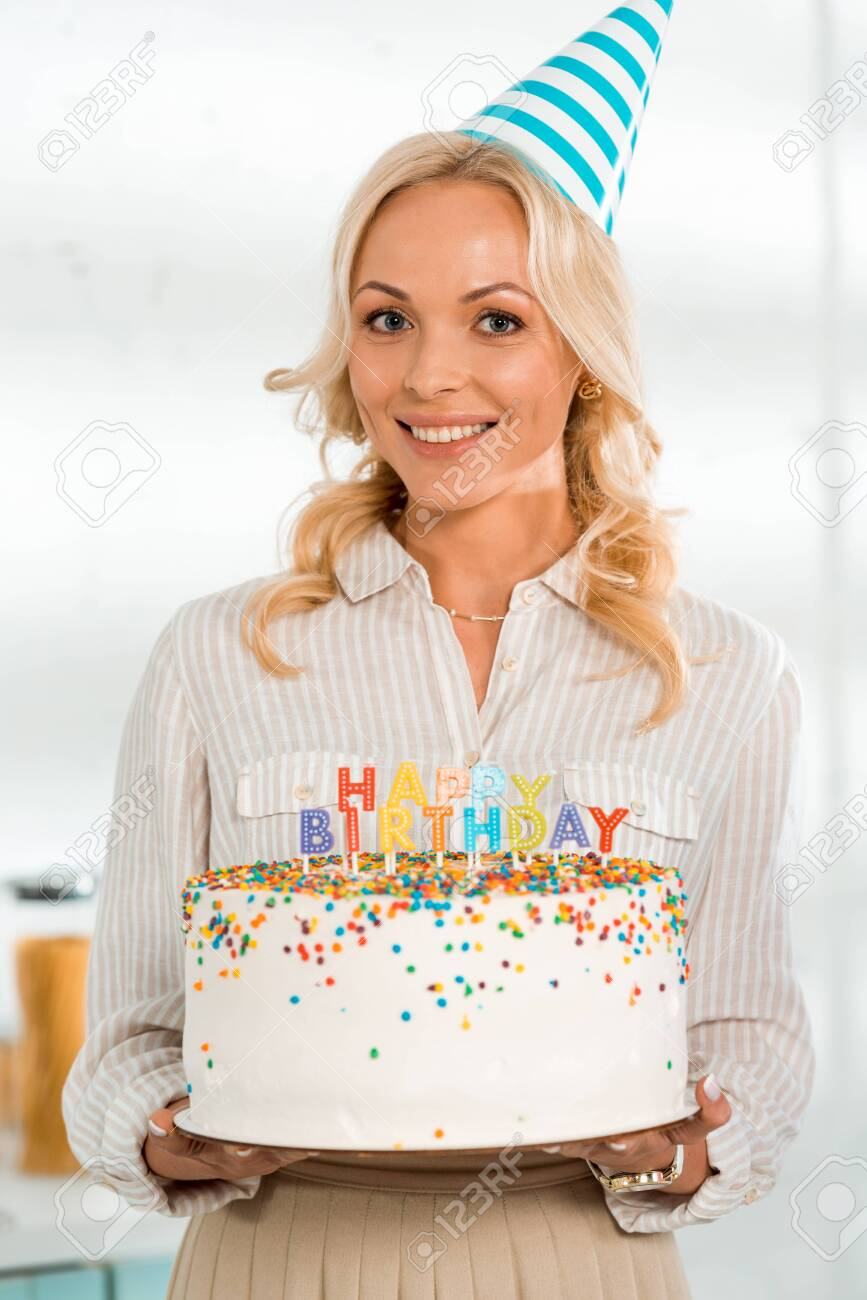 Happy Woman In Party Cap Holding Birthday Cake With Colorful Stock Photo Picture And Royalty Free Image Image 136058294