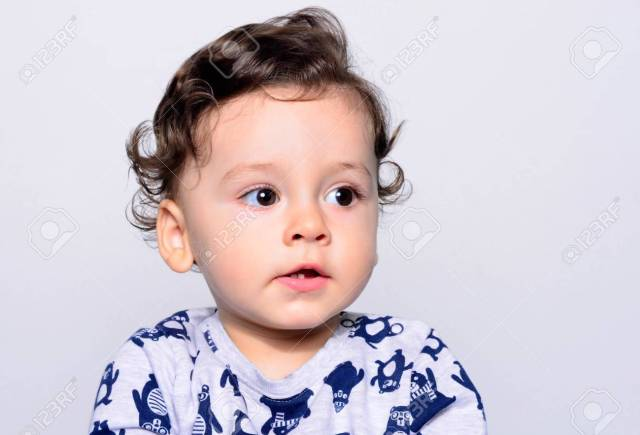 portrait of a cute curly hair baby boy looking away. adorable..