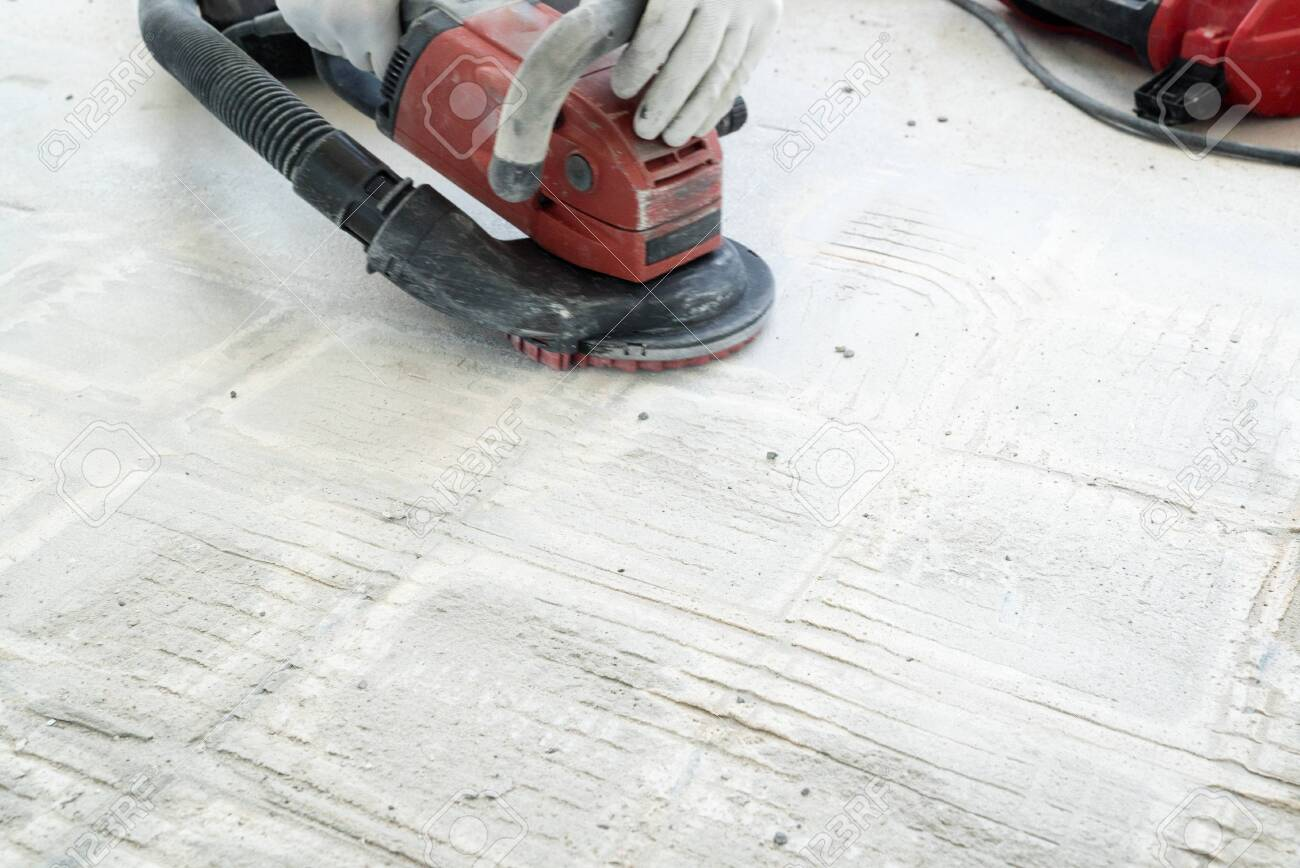https www 123rf com photo 130070707 a construction worker uses a power concrete grinder for removing tile glue and resin during renovati html