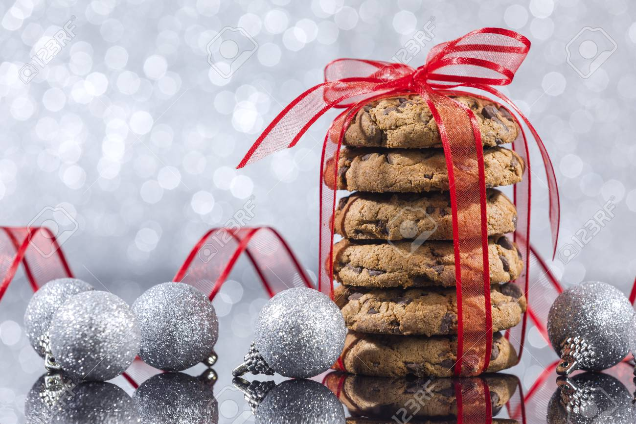 stack of chocolate chip cookies with christmas ornaments reflection