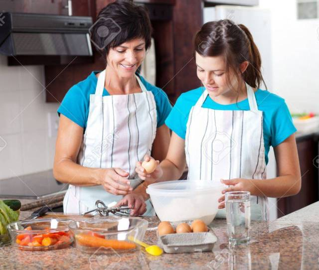 Middle Aged Mother Teaching Teen Daughter Baking In Kitchen Stock Photo