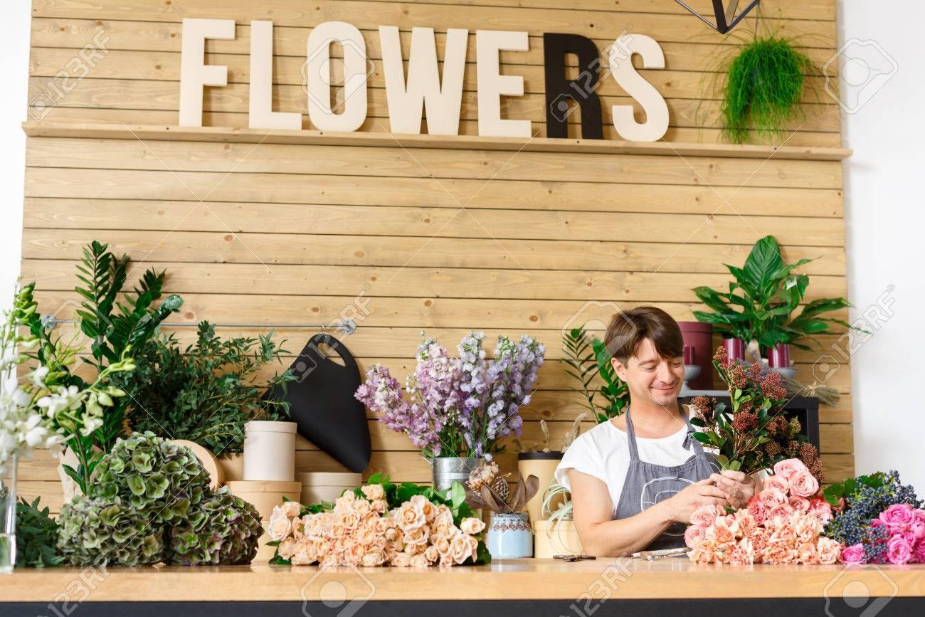 fleuriste decision homme bouquet de roses au comptoir bureau dans magasin de fleurs man assistant ou proprietaire floral studio de design ce qui rend les