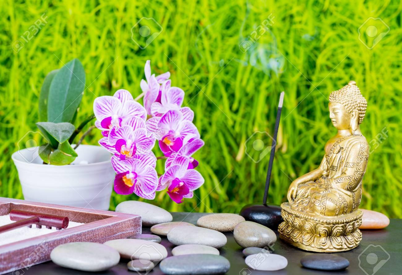 fond de jardin zen avec bouddha fleur d orchidee rateau sable et pierres zen
