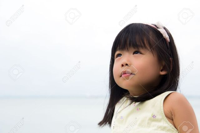 Portrait Of Little Asian Girl With Eyes Looking Up To Sky Stock Photo 11533327