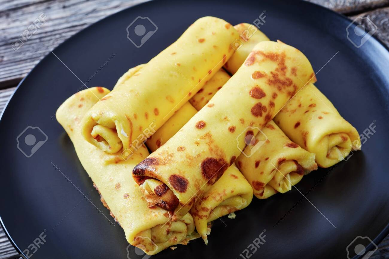 https www 123rf com photo 118870625 close up of crepe roll ups with cream cheese filling on a black plate on an old wooden table view fr html