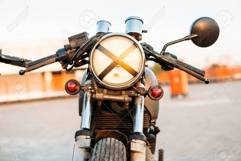 One Vintage Custom Motorcycle Cafe Racer Motorbike With Tape Cross Over Headlight Optic On Empty Rooftop