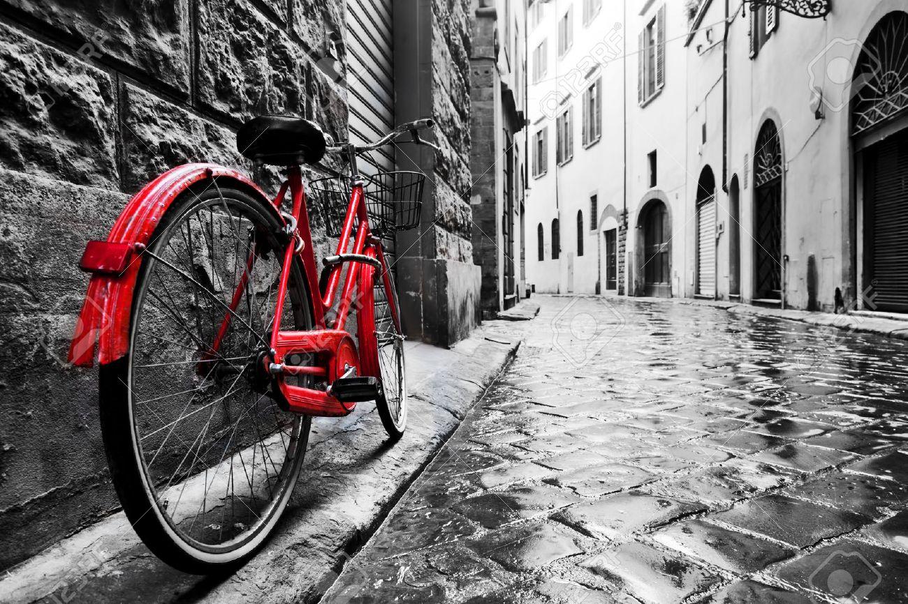 retro vintage rotes fahrrad auf gepflasterten strasse in der altstadt farbe in schwarz und weiss alte charmante fahrrad konzept
