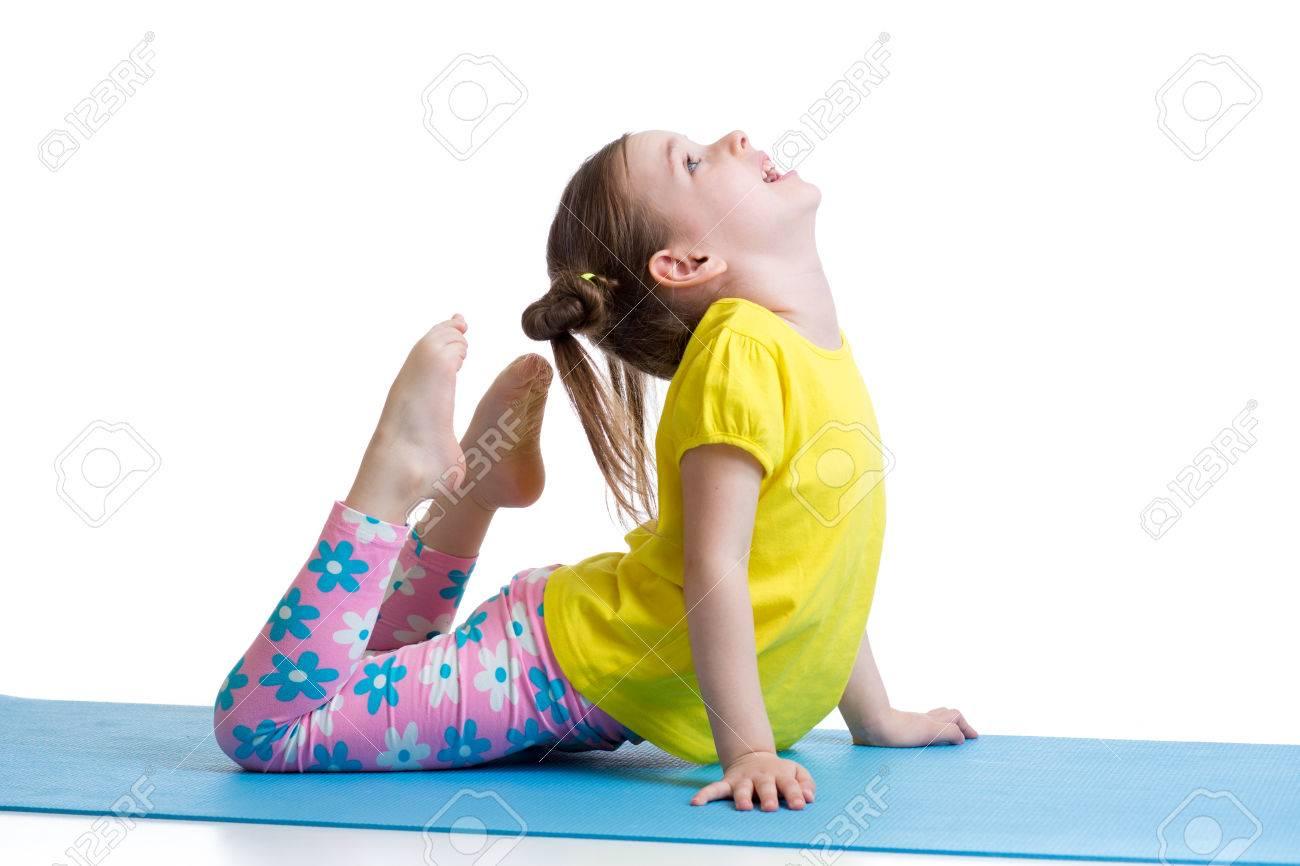 fille de faire des exercices de gymnastique pour enfants sur le tapis isole