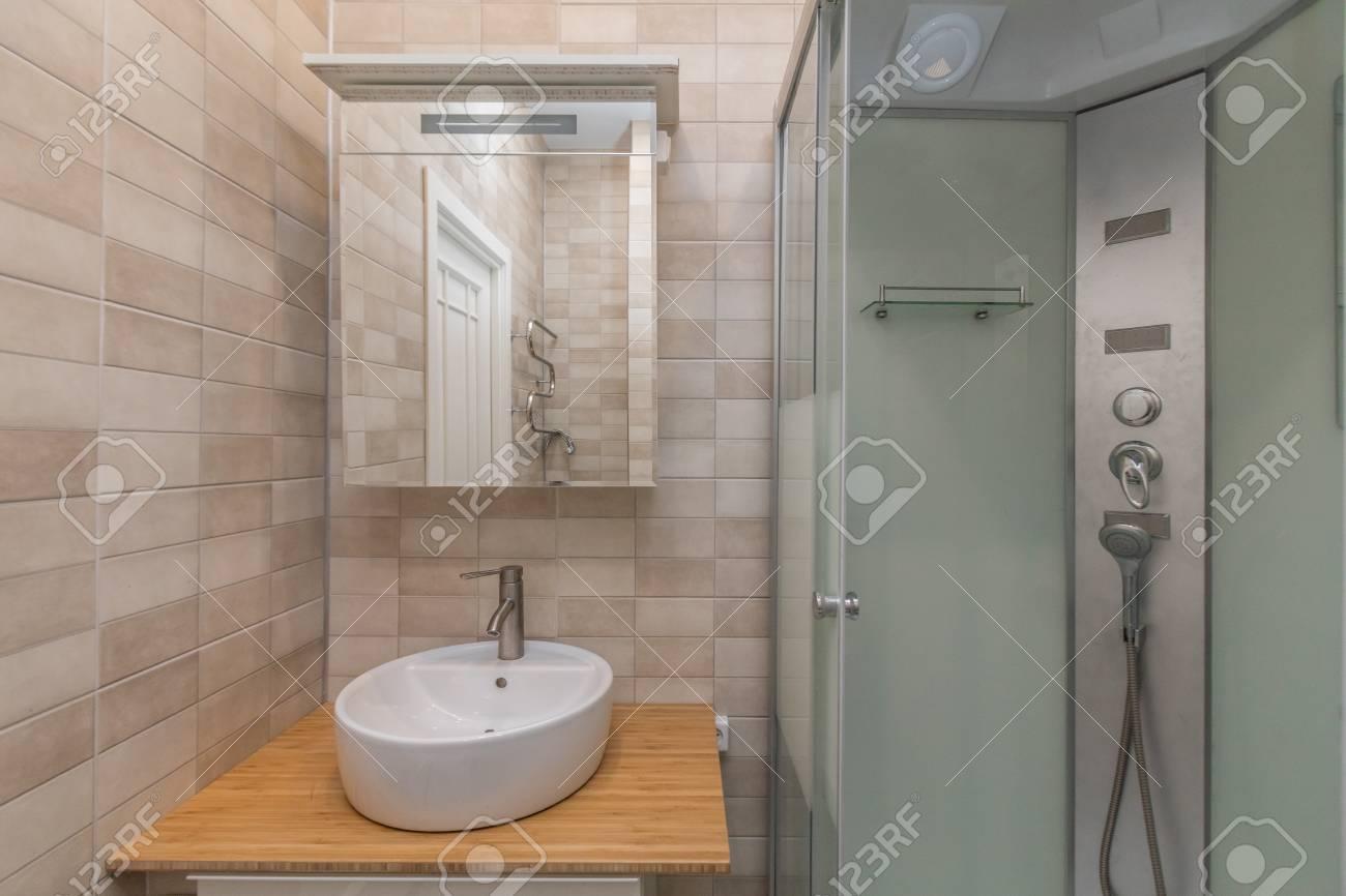 petite salle de bain beige avec cabine de douche et evier banque d images et photos libres de droits image 99514688