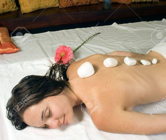 Stock Photo Woman Closes Her Eyes And Relaxes As She Gets A Hot Stone Massage Vertically Framed Photograph