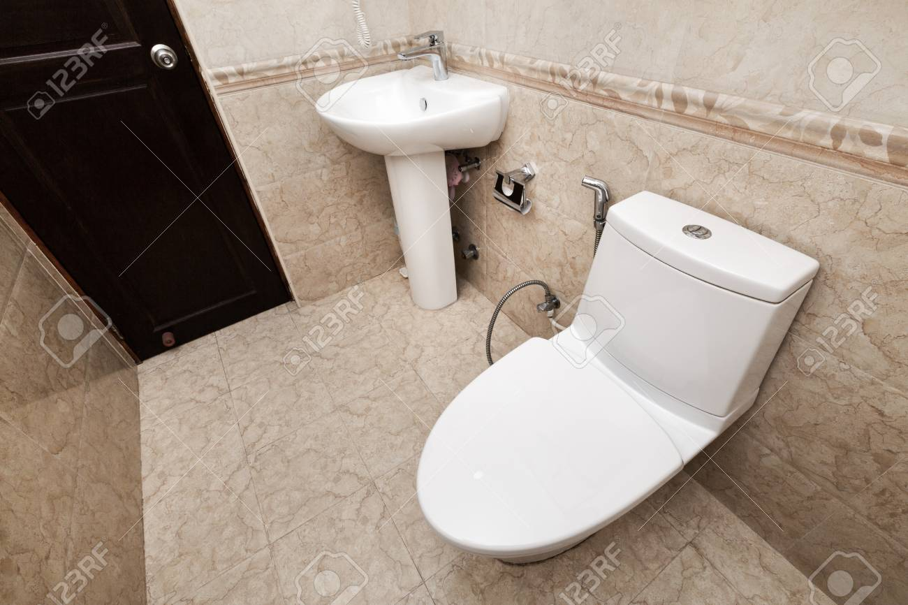 white toilet bowl and sink with faucet in a bathroom interior