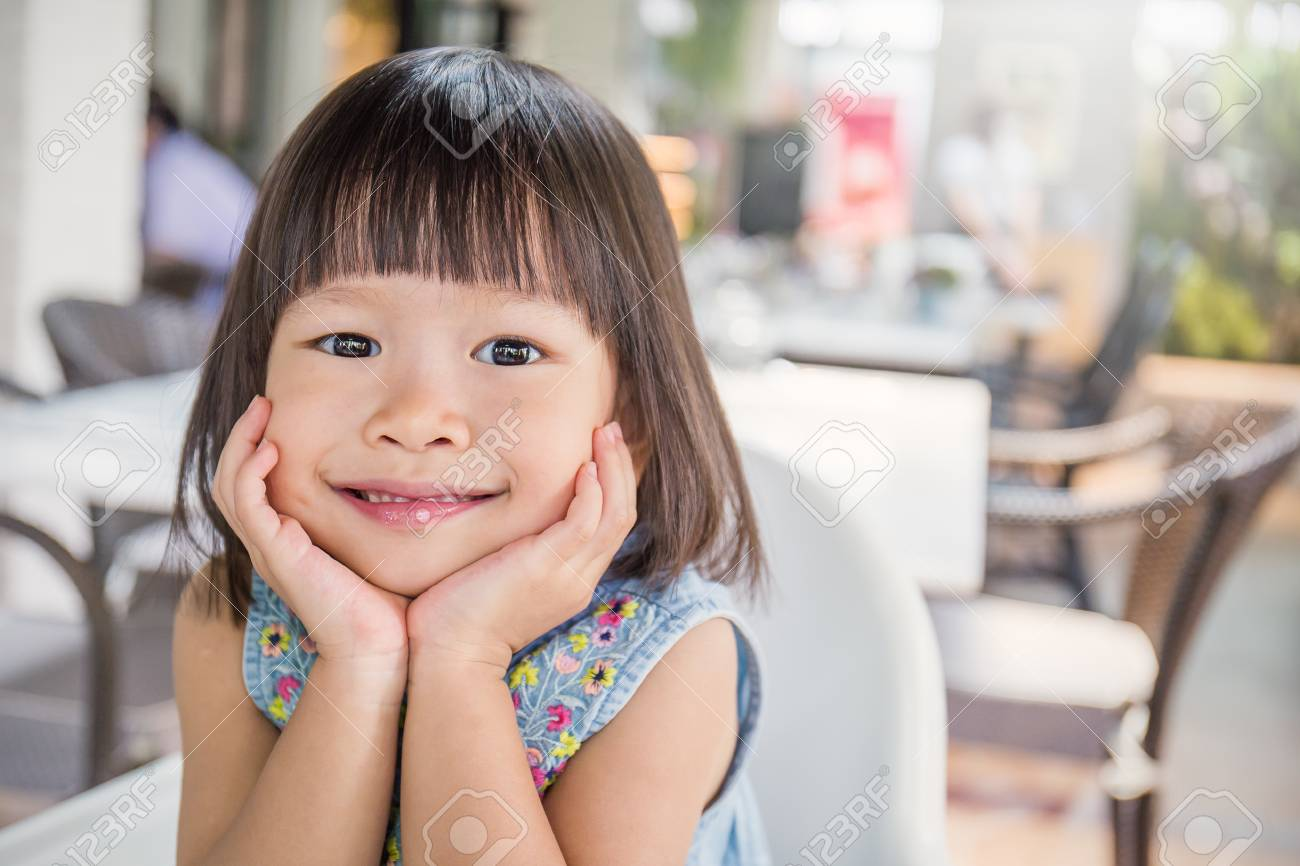 Portrait Of Little Cute Asian Girl Lovely Small Asian Girl With Her Hands Holding Her