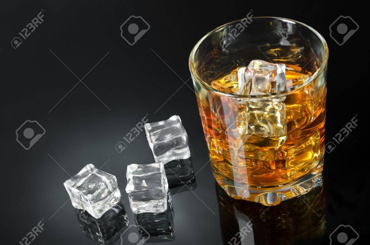 un verre de whisky avec des glacons sur un fond noir
