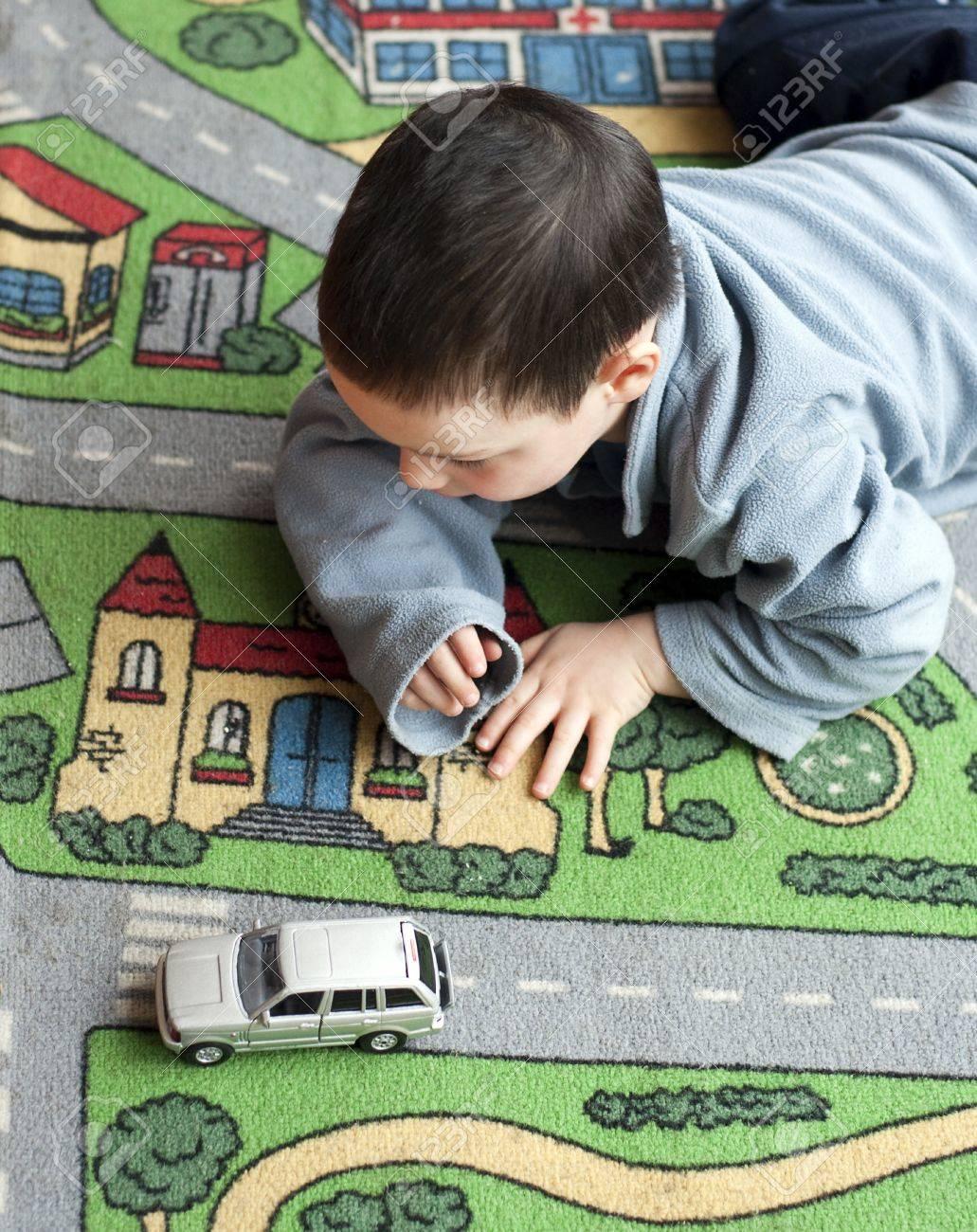 petit garcon d enfant jouant sur un tapis sur le theme de la route avec une voiture jouet