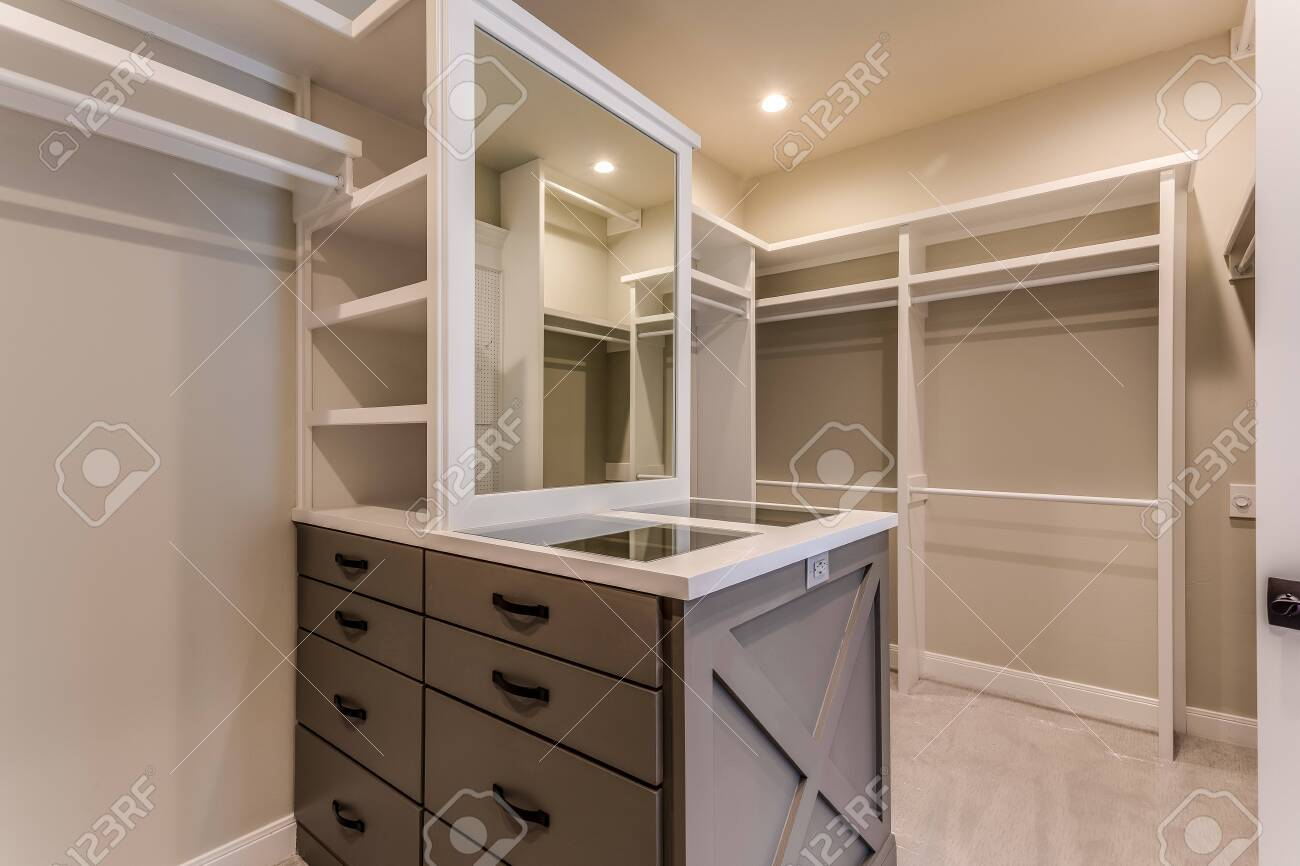 amazing master closet with glass top island and led lighting