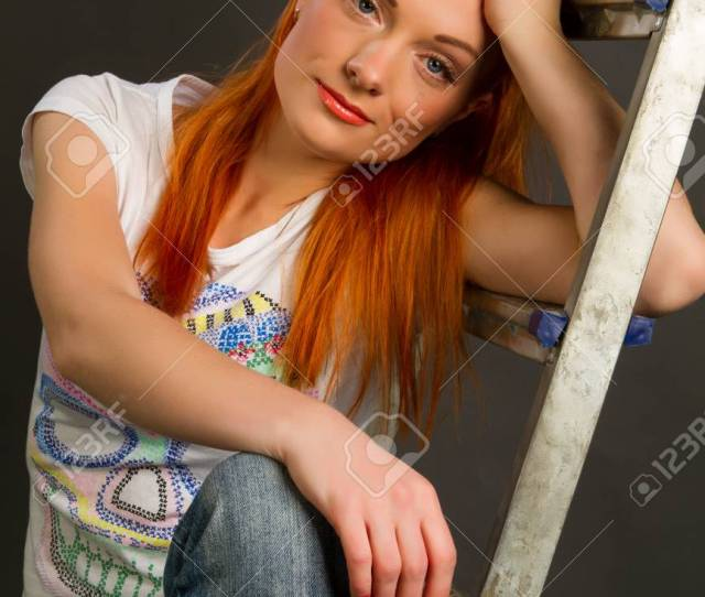 Beautiful Young Red Haired Girl Leaning On A Ladder On A Gray Background Stock Photo