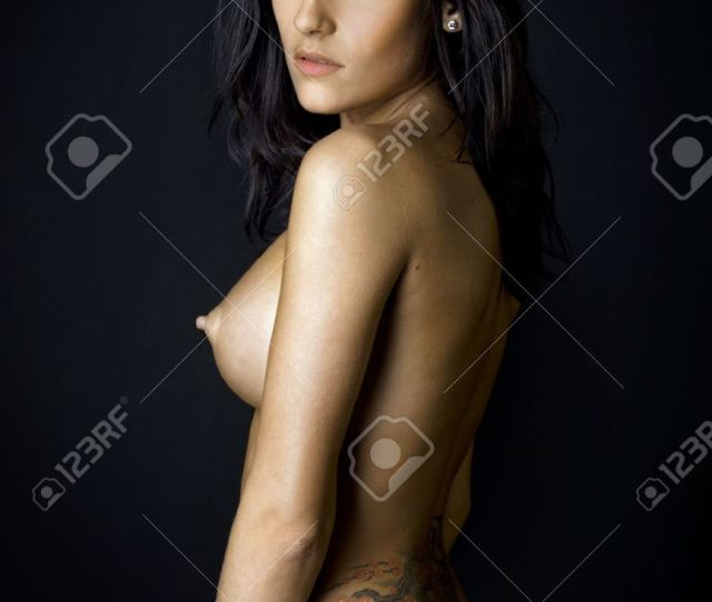 Back Of The Beautiful Naked Woman With Tattoo Photo With Dark Background Stock Photo