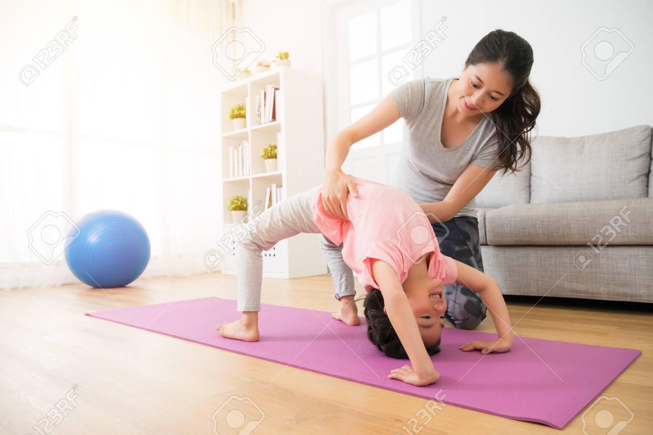 un professeur de gymnastique a la maison assiste les beaux enfants en train de faire du yoga et les mains aide a maintenir la taille du corps des enfants avec soin pour