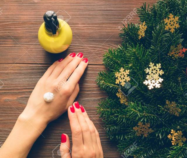 Female Hands With Red Nail Polish A Bottle Of Hand Cream And Christmas Decorations On