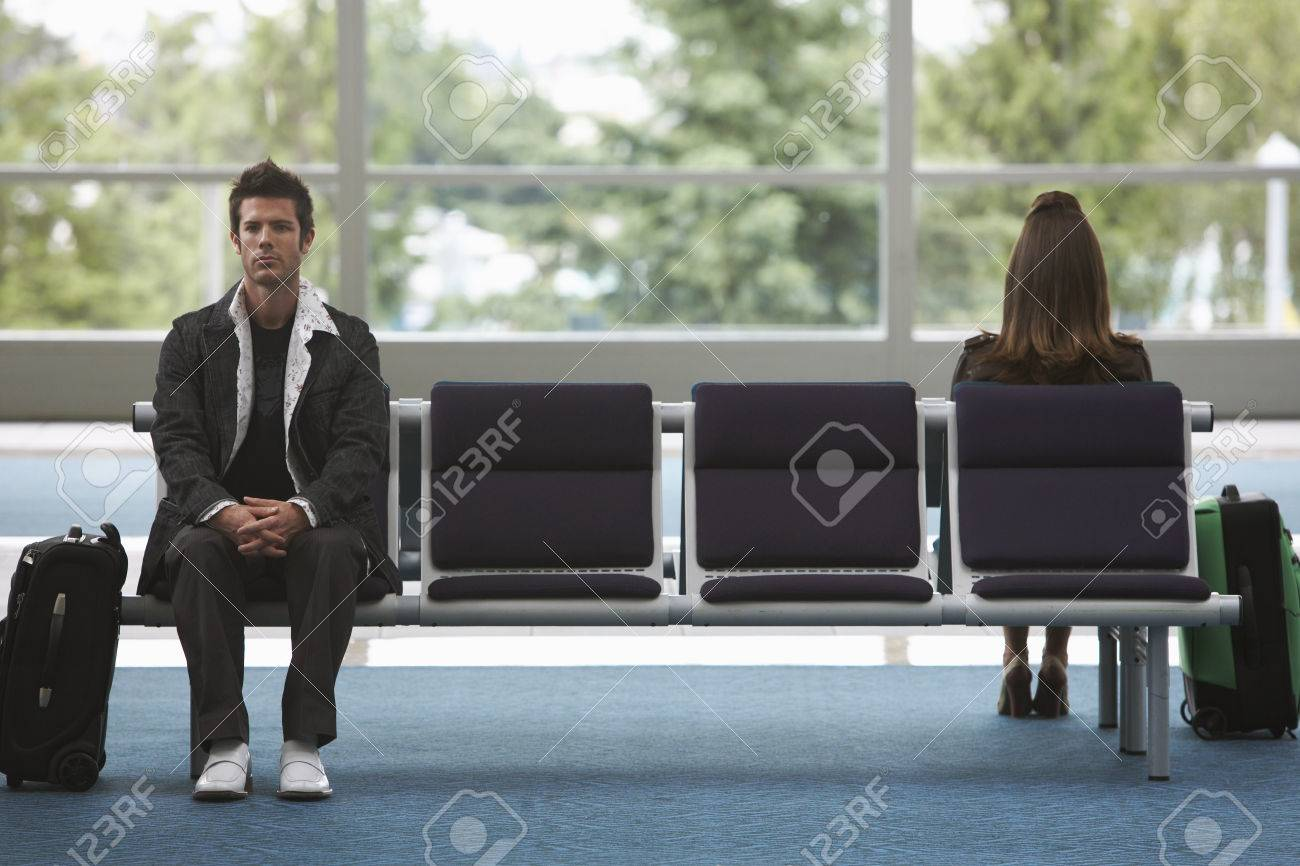 Man And Woman In Airport Waiting Area Stock Photo, Picture And ...