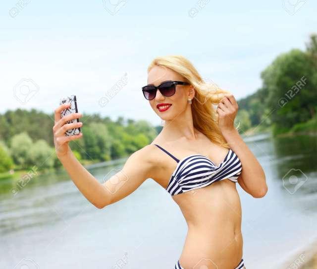 Beautiful Blonde Girl In A Bikini On The Beach Makes Selfie Beautiful Blonde Woman On