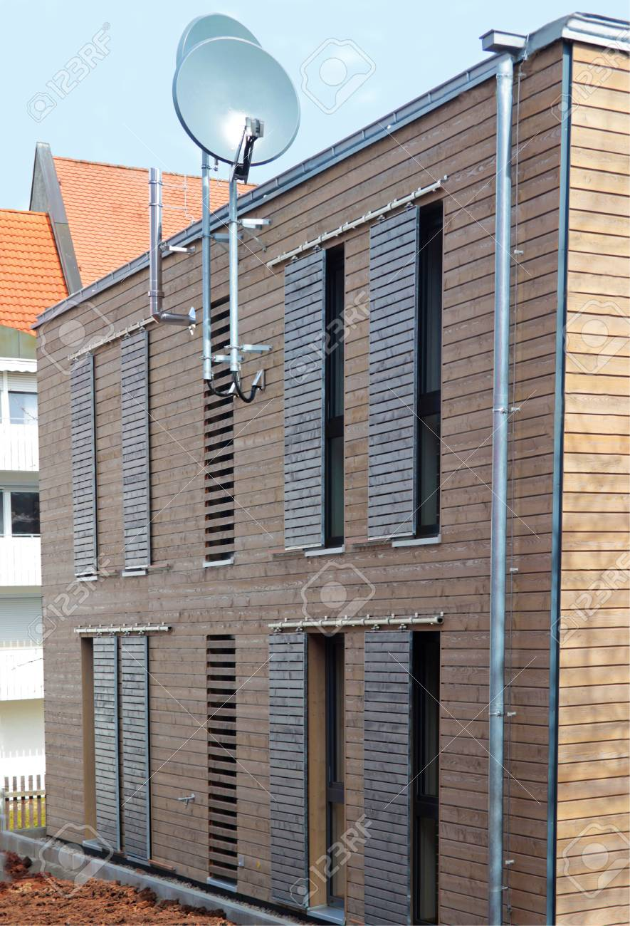 Modern Wooden House With Sliding Window Shutters And Two Satellite