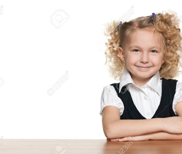 A Little Blonde Schoolgirl Sits At A School Desk On The White Background Stock Photo
