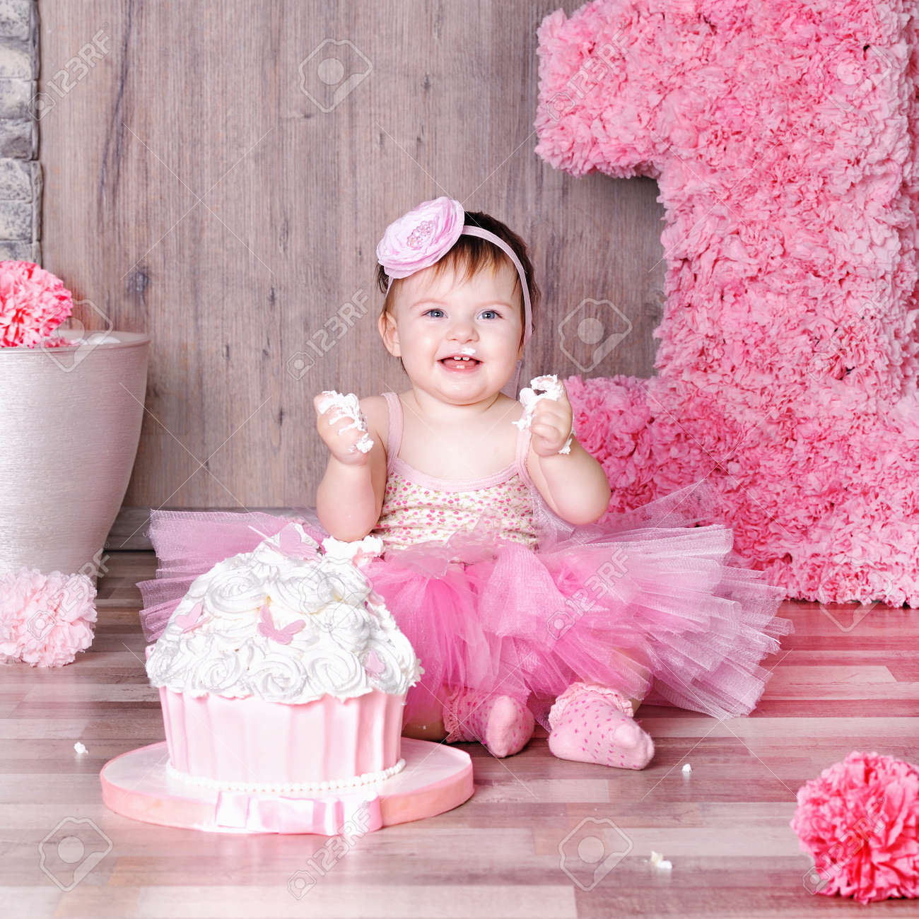 1 Year Baby Girl In Pink Dress With Her First Birthday Cake Stock Photo Picture And Royalty Free Image Image 86750094