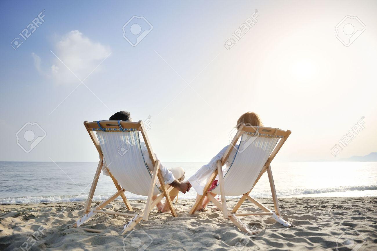 couple romantique heureux sur transat detendre et profiter de coucher de soleil sur la plage