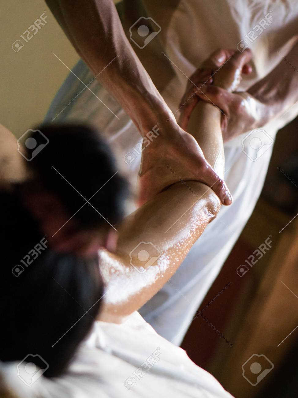 Professional Masseur Doing Deep Tissue Oiled Massage To A Girl At Ayurveda Massage Session Stock Photo