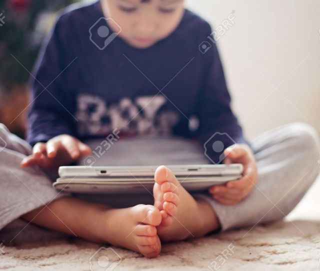 Cute Little Boys Feet Boy Playing On Tablet In Front Of A Christmas Tree Stock