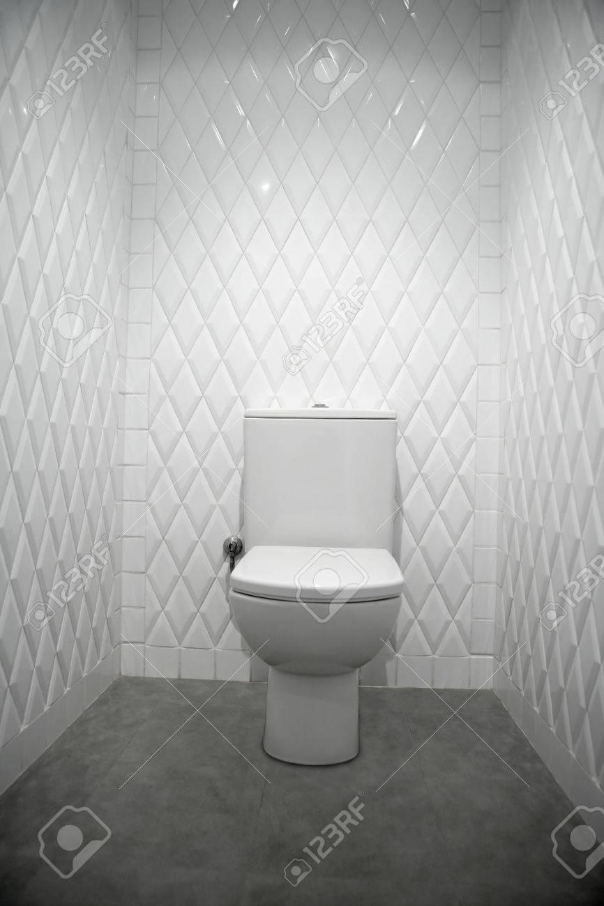 toilet in a white narrow room diamond shape tiles