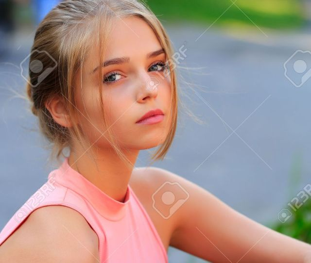 Pretty Sexy Young Woman Or Girl With Tied In Bun Blonde Hair In Pink Shirt With