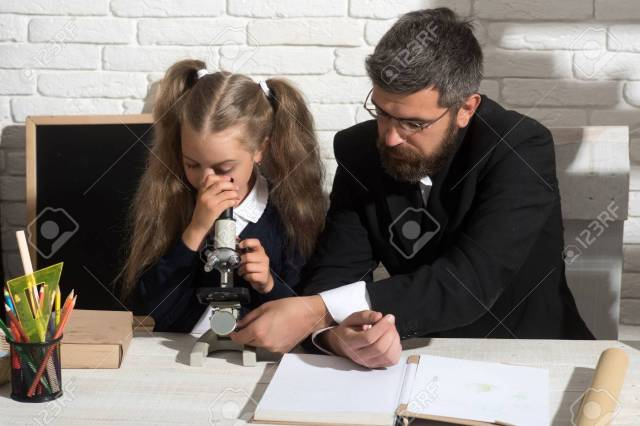 Girl And Man Sit By Desk And Looks Into Microscope Teacher And Schoolgirl In Study