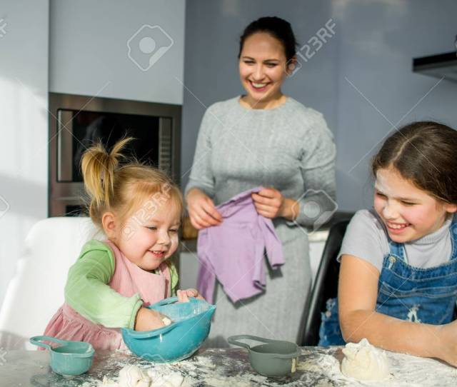 Mom Teaches Two Little Daughters To Cook From Dough Children With Pleasure Are Engaged In