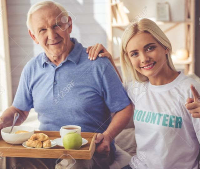 Beautiful Young Girl Volunteer Is Giving Food To Handsome Old Man Both Are Looking At