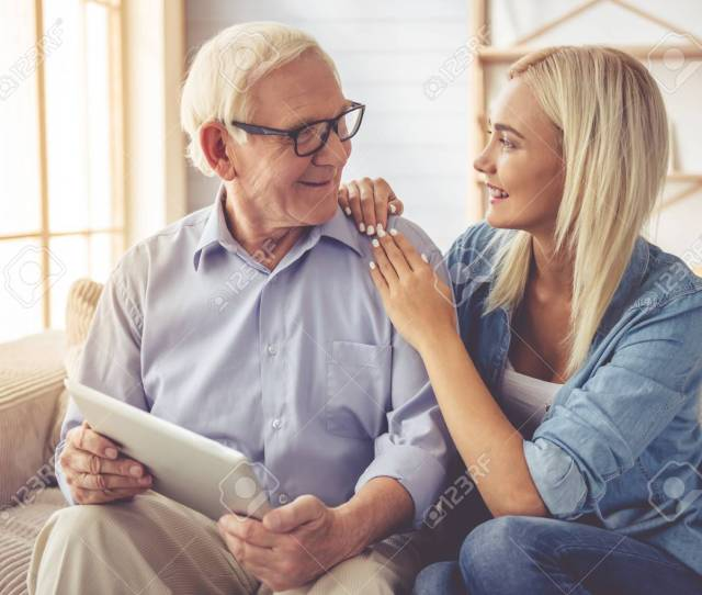 Handsome Old Man And Beautiful Young Girl Are Using A Digital Tablet Talking And Smiling