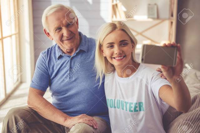 Beautiful Young Girl Volunteer And Handsome Old Man Are Doing Selfie Using A Smart Phone And