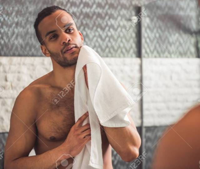 Handsome Naked Afro American Man Is Wiping His Face Using A Towel While Looking Into The