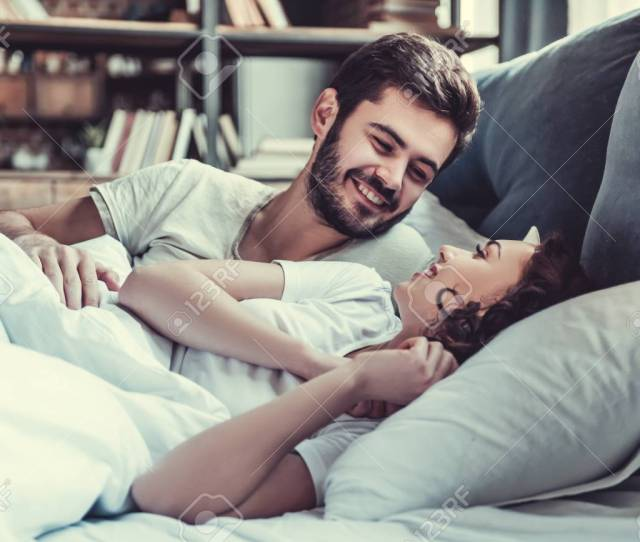Passionate Love Happy Young Couple Hugging And Smiling While Lying On The Bed In A