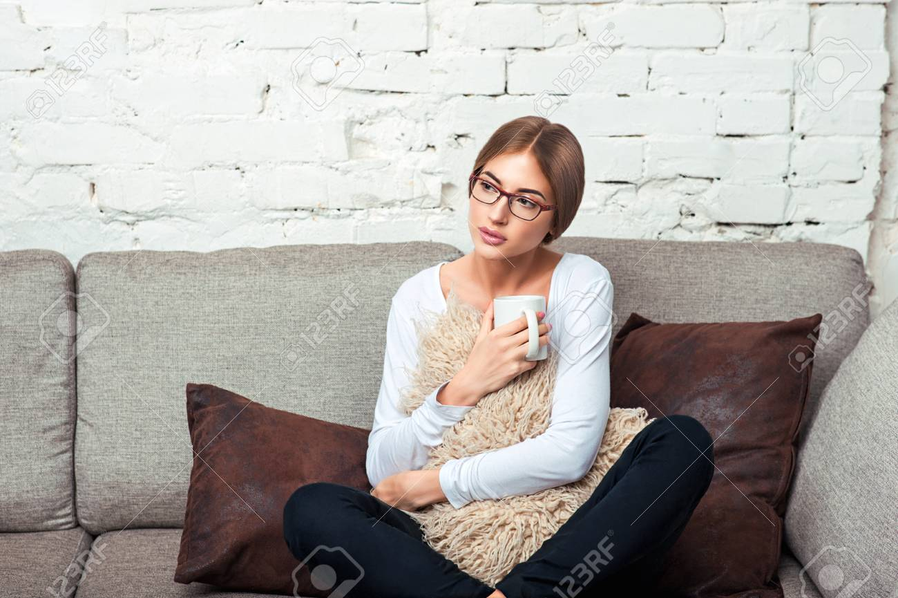 https www 123rf com photo 98002433 young beautiful woman in glasses hugging a pillow holding a cup of hot tea and sitting on the couch html