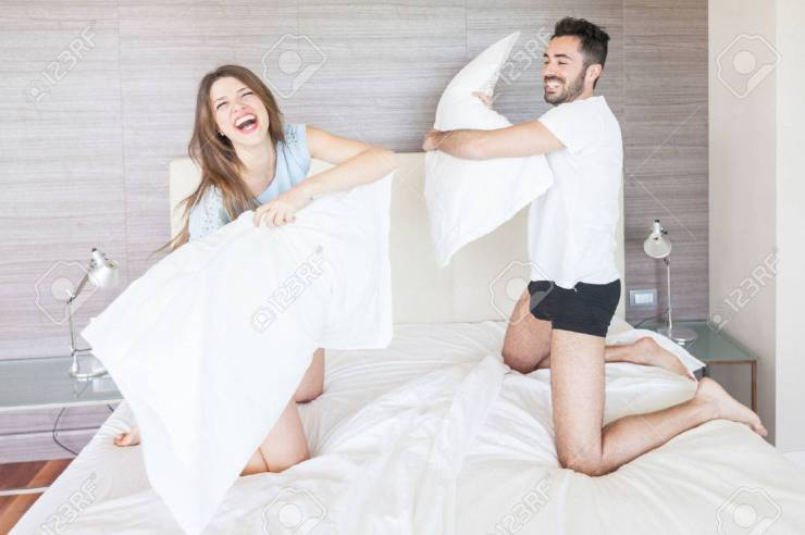 Happy Couple Having Pillow Fight In Hotel Room Stock Photo, Picture And  Royalty Free Image. Image 27492103.