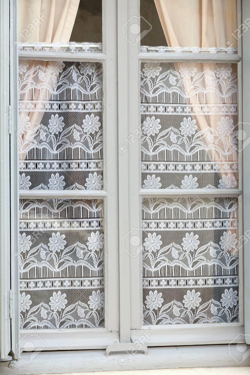 la fenetre blanche avec decoration de vieux rideaux de dentelle
