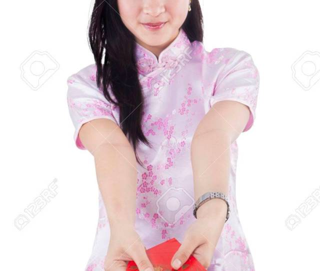 Beautiful Chinese Girl Wearing Traditional Chinese Dress And Giving Red Envelope To The Camera Stock Photo