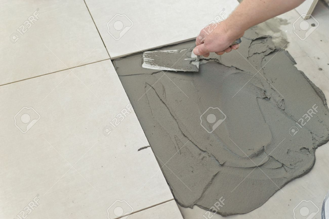 laying ceramic tiles troweling mortar onto a concrete floor