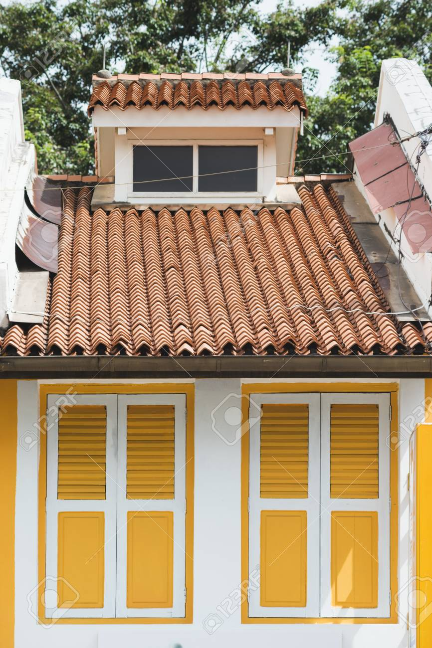 Bright Yellow Window Shutters Of Small House Closed By Sunny