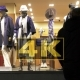 Silhouettes Of Pedestrians In Front Of Mannequins In Window Of Shop