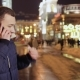 Young Handsome Guy Talks on Phone at Night City Background