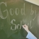 Girl Schoolgirl Writes on the Blackboard Phrase - Good Bye School. Farewell To the School.