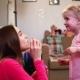 Mother Blows a Soap Bubble for Her Little Daughter. The Funny Baby Pops It By Her Hands